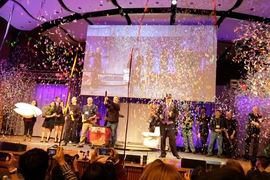 "Mechanical engineering professor David Wallace (right of center in top hat) was surprised with a tribute video for his 20 years of teaching the ""product engineering processes"" class, before course instructors shot streams of confetti over the audience."
