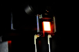 A proof-of-concept device built by MIT researchers demonstrates the principle of a two-stage process to make incandescent bulbs more efficient. This device already achieves efficiency comparable to some compact fluorescent and LED bulbs.