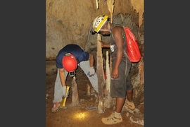 University of Massachusetts professor Stephen Burns (left) and Malagasy student Peterson Faina cutting a stalagmite at Anjohibe Cave.
