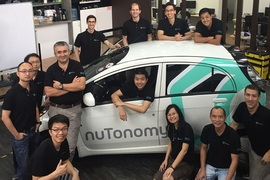 The nuTonomy team, including Emilio Frazzoli (third from left, standing), with one of their driverless cars