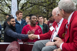 Peter Miller '62 (left) and Oliver Smoot '62 (right) shake hands with spectators, while in the grand marshall's car.