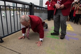 "Oliver Smoot '62, whose body length was used to measure the bridge over the Charles River near MIT, in a noted 1958 prank by MIT students, demonstrates how he did it. Smoot served as grand marshall in the ""Crossing the Charles"" procession and competition."