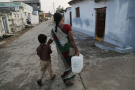 A woman and her son, who live in Chellur, India, walk home with the reverse-osmosis-treated water she bought at Chellur's community desalination plant.