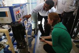 CB Nataraja, a representative from Tata Projects Limited, shows PhD candidate Natasha Wright one of the company's existing on-grid, reverse-osmosis desalination systems in a rural village north of Hyderabad, India.