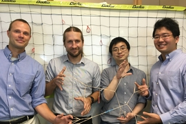 Left to right: Professors Bradley Olsen and Jeremiah Johnson, postdoc Rui Wang, and grad student Ken Kawamoto demonstrate polymer elasticity using rubber bands.