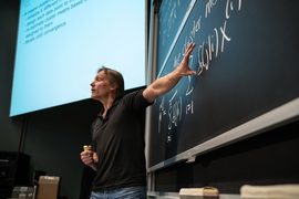 Tommi Jaakkola, a professor of electrical engineering and comptuer science at MIT, tosses chocolates to students during Introduction to Machine Learning, or 6.036.