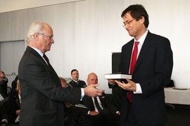 His Majesty King Carl XVI Gustaf of Sweden, left, meets MIT professor of physics Max Tegmark, right, during the king's visit to MIT on Friday, May 5. The Stockholm-born Tegmark conducted an exchange of gifts with the Swedish delegation, which included multiple books by MIT faculty and about MIT.
