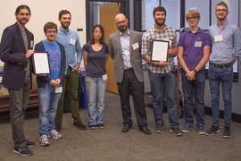 At center is Mike Tarkanian, a senior lecturer in the Department of Materials Science and Engineering and MADMEC competition organizer. Flanking him are two teams, Geoworks (left) and DUMBLEDORE (right), which split second and third place prizes of $7,000 and $5,000.