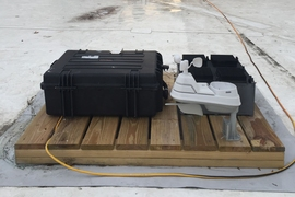 The team's test device, which has been deployed on the roof of an MIT building for several months, was used to prove the principle behind their new energy-harvesting concept. The test device is the black box at right, behind a weather-monitoring system (white) and a set of test equipment to monitor the device's performance (larger black case at left).