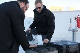 Professor Michael Strano (left) and graduate student Anton Cottrill check on their test device on the roof of an MIT lab building.