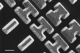 "Scanning Electron Microscope image shows a few of the carefully designed shaped of the chalcogenide glass deposited on a clear substrate. The shapes, which the researchers call ""meta-atoms,"" determine how mid-infrared light is bent when passing through the material."