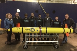 Scientists get ready to load an AUV onto a research vessel for a test of navigation and sensing algorithms at sea.
