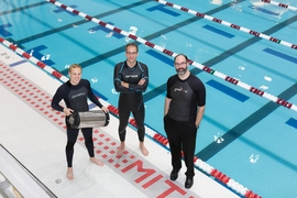 From left, graduate student Anton Cottrill, Professor Jacopo Buongiorno and Professor Michael Strano try out their neoprene wetsuits at a pool at MIT's athletic center. Cottrill is holding the pressure tank used to treat the wetsuits with xenon or krypton.
