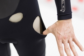 Holes in a wetsuit reveal the thickness of the neoprene material. The new MIT-developed treatment could provide the same amount of insulation with just half the thickness, the researchers say.