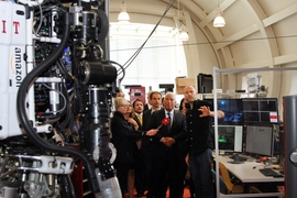 Prime Minister António Costa (center) visited the Computer Science and Artificial Intelligence Laboratory and met members of the Robot Locomotion Group, including Professor Russ Tedrake (right), who described the Atlas robot (left), which competed in the DARPA Robotics Challenge.