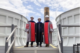 Kripa Varanasi, associate professor of mechanical engineering, poses on the roof of the Central Utility Plant with the two doctoral students who led the research project, Maher Damak (left) and Karim Khalil (right), just after receiving their doctoral hoods this week.