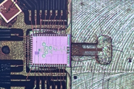 The clock transmitter chip (pink) wired to a circuit board package. Connected is a metal gas cell (right), in which a 231.061 GHz signal generated from the chip excites the rotation of carbonyl sulfide molecules. When the molecules reach peak rotation, they form a sharp signal response. That frequency can then be divided down to exactly one second, matching the official time from atomic clocks, th...