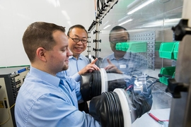 Cadenza Innovation employees Jay Shi, vice president of research and development, and Joshua Liposky, associate director of battery systems, use a moisture-free glove box while working with battery materials in the company's state-of-the art R&D labs in Bethel, Connecticut.