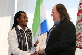 Ethan Zuckerman, head of the MIT Media Lab's Center for Civic Media, and David Sengeh, PhD '16, Sierra Leone's Chief Innovation Officer, exchange a memorandum of understanding for collaborative work.