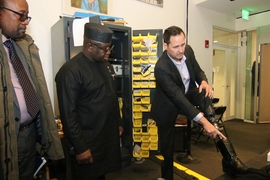 Hugh Herr, director of the Media Lab's Biomechatronics group, right, shows Sierra Leone President Julius Maada Bio, center, some of the features of his own high-tech prosthetic leg, developed at the lab.