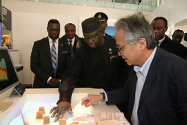 Prof. Hiroshi Ishii, right, Director of the Tangible Media Group and Associate Director of the Media Lab, demonstrates  to Sierra Leone President Julius Bio, center, a system his lab developed for modeling the effects of changes in a landscape.