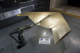 Wing assembly is seen under construction, assembled from hundreds of identical subunits. The wing was tested in a NASA wind tunnel.