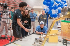 A 2.007 instructor measures the speed at which a student's robot spins a wheel — one of several point-scoring tasks.