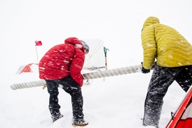 Retrieving an ice core section from the drill barrel during a west Greenland snowstorm, west Greenland Ice Sheet.