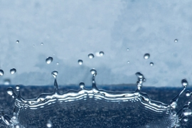Droplets that land on a specially prepared surface with tiny ring-shaped patterns splash upward in a bowl shape, as seen in this photo, instead of spreading out over the surface, thus minimizing the water's contact with the surface.