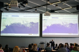 "Professor John Sterman displays maps showing the consequences of sea-level rise on various coastal cities, as part of the ""SimPlanet"" event at MIT."