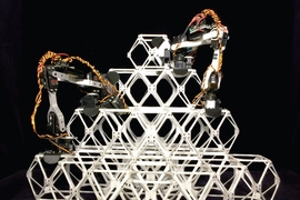 Photo shows two prototype assembler robots at work putting together a series of small units, known as voxels, into a larger structure.