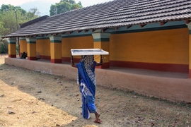 A woman carrying a Khethworks solar panel. The efficiency of Khethworks' groundwater pump enables it to be powered by smaller panels, making the system portable.