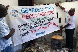 Residents hold a sign announcing a neighborhood meeting as part of Liberia's effort to stop the spread of Ebola, in October 2014. A new study shows how a volunteer outreach campaign helped people understand and cooperate with government efforts to control the disease.