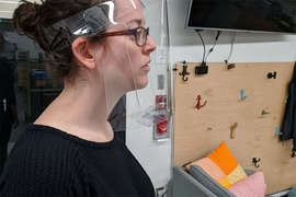 Robyn Goodner, who serves as a Maker Technical Specialist for Project Manus, models the face shield design in the Metropolis Makerspace.