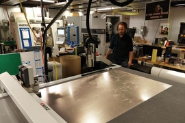 Graduate student Zach Fredin operates the Zund large-format cutter in MIT's Center for Bit and Atoms. The machine was used to make prototypes of the face shield.