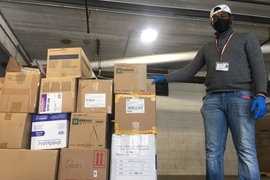A staff member from Cambridge Health Alliance accepts a delivery from MIT.