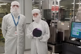 MIT researchers demonstrated a method to manufacture carbon nanotube transistors in commercial facilities that fabricate silicon-based transistors. This photograph shows Anthony Ratkovich, left, and Mindy D. Bishop, who is holding an example of a silicon wafer.