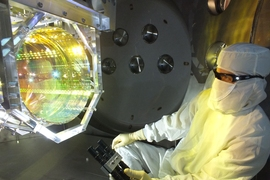 MIT physicists have observed that LIGO's 40-kilogram mirrors can move in response to tiny quantum effects. In this photo, a LIGO optics technician inspects one of LIGO's mirrors.