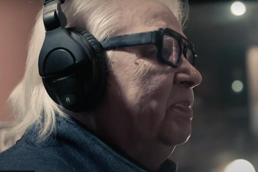 A profile portrait of Ojibwe Elder Duke Redbird, wearing headphones