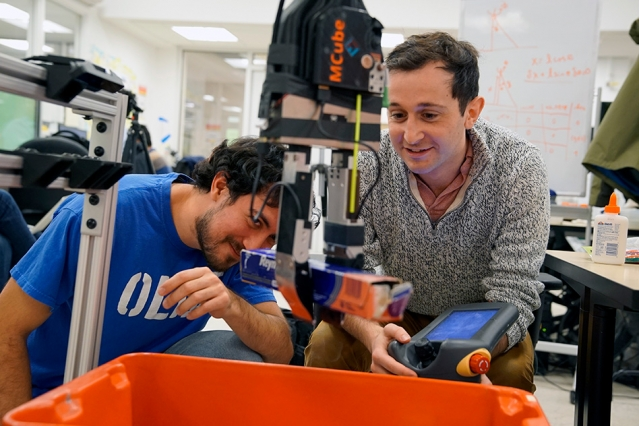 Elliott Donlon (left) and Francois Hogan (right) work with the robotic system that may one day lend a hand with this household chore, as well as assist in other picking and sorting tasks, from organizing products in a warehouse to clearing debris from a disaster zone.